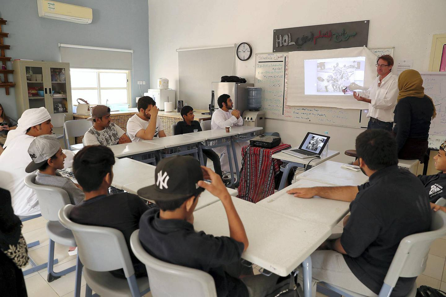 RAS AL KHAIMAH , UNITED ARAB EMIRATES , FEB 21  – 2018 :- Guy Brooksbank ( white shirt right side )  teaching students from Saeed Bin Jubair Secondary School how to take photograph during the photography workshop at the school campus in Ras Al Khaimah. ( Pawan Singh / The National ) For News. Story by Ruba Haza