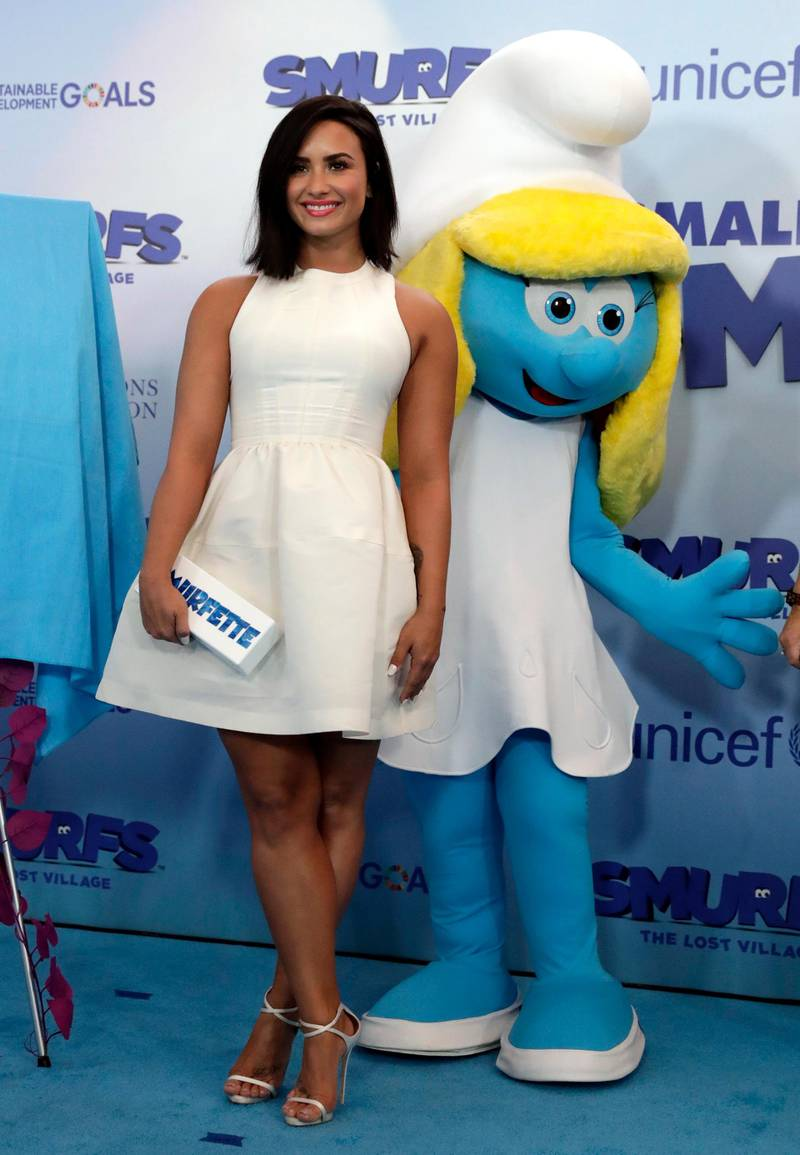 epa05856448 US singer/actress Demi Lovato smiles in front of Smurfette at the International Day of Happiness in conjunction with 'Smurfs: The Lost Village' at United Nations headquarters in New York, New York, USA, 18 March 2017. Lovato is the dubbing voice of the character 'Smurfette' in the upcoming movie 'Smurfs: The Lost Village'.  EPA/JASON SZENES