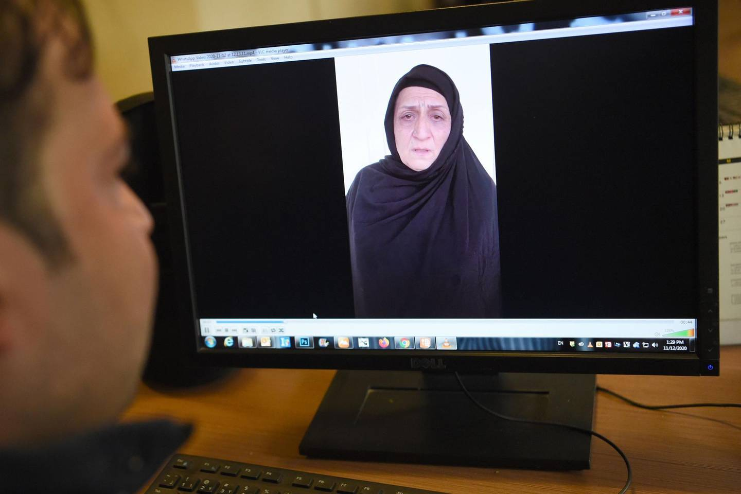 In this picture taken on November 12, 2020, a man watches a video of Afghan woman Nasreen, who walked free from jail in September after confessing to being members of the Taliban's ultra-violent Haqqani network, on a computer screen in Kabul. Female assassins who lured an Afghan security official to his death with promises of sex before shooting him and dumping his body at a cemetery are among thousands of Taliban criminals freed as part of a fragile peace plan. - TO GO WITH 'Afghanistan-conflict-Taliban-women-prisoners, FOCUS' by Elise BLANCHARD  / AFP / Wakil KOHSAR / TO GO WITH 'Afghanistan-conflict-Taliban-women-prisoners, FOCUS' by Elise BLANCHARD