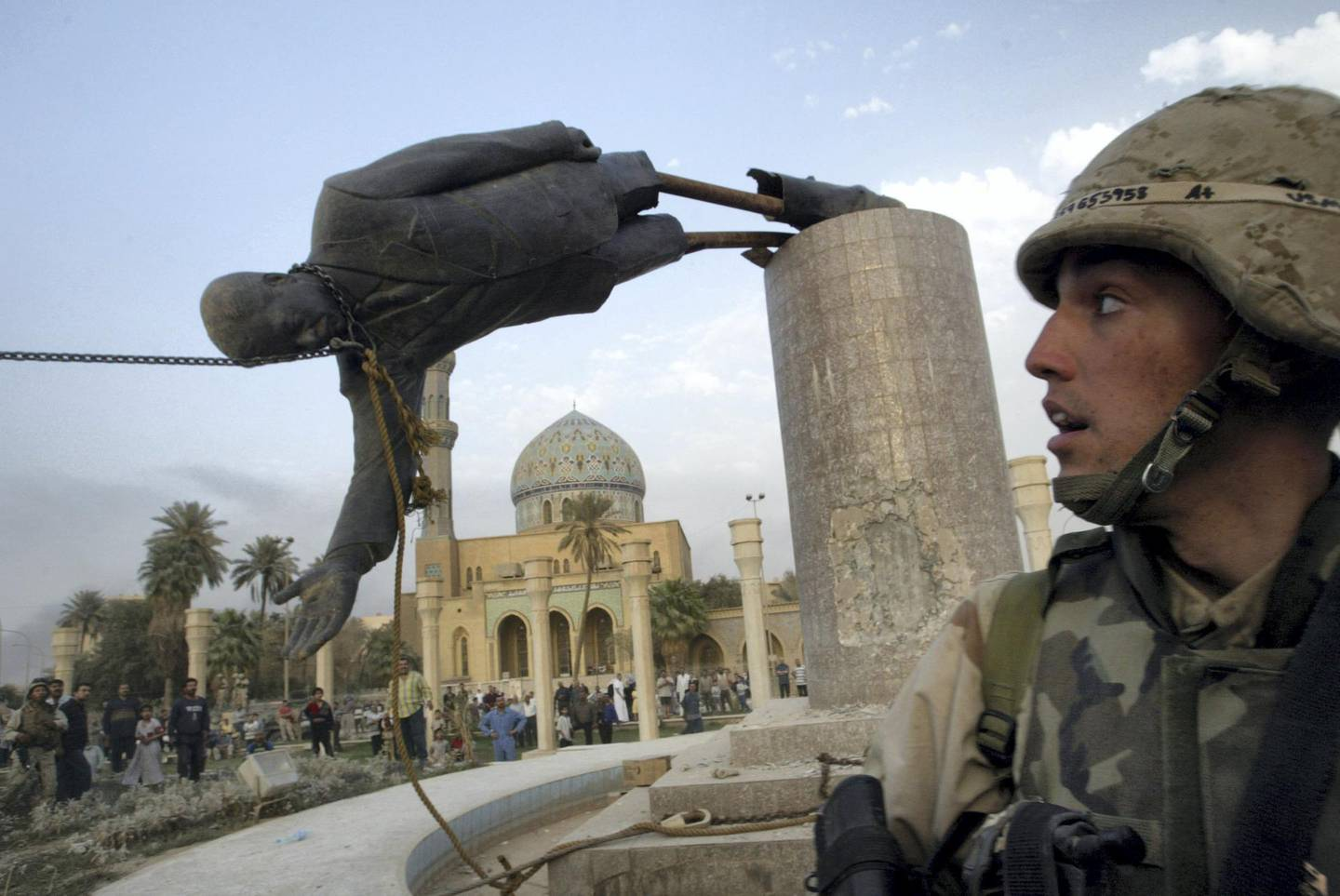 A U.S. soldier watches as a statue of Iraq's President Saddam Hussein falls in central Baghdad in this April 9, 2003 file photo. REUTERS/Goran Tomasevic  AS/CRB