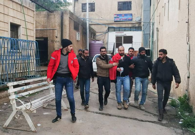 """EDITORS NOTE: Graphic content / A handout picture obtained from the official Syrian Arab News Agency (SANA) on February 20, 2020 shows a recovering Syrian Oxfam aid volunteer, wounded the previous day in an attack in Syria's southern province of Daraa, walking out of a hospital in the town of al-Yadudah after being discharged on February 19th. Oxfam said that two of the British aid group's local workers died in an attack yesterday in the government-held region of Daraa. The aid group said the two Syrian Oxfam aid workers were both killed when their vehicle was attacked by an unidentified armed group, adding that another Oxfam volunteer was also injured. -  == RESTRICTED TO EDITORIAL USE - MANDATORY CREDIT """"AFP PHOTO / HO / SANA"""" - NO MARKETING NO ADVERTISING CAMPAIGNS - DISTRIBUTED AS A SERVICE TO CLIENTS ==  / AFP / SANA / - /  == RESTRICTED TO EDITORIAL USE - MANDATORY CREDIT """"AFP PHOTO / HO / SANA"""" - NO MARKETING NO ADVERTISING CAMPAIGNS - DISTRIBUTED AS A SERVICE TO CLIENTS =="""