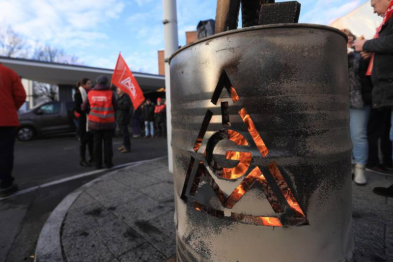 The IG Metall logo sits on a burning brazier barrel during a 24 hour strike called by the labor union outside the BMW Motorrad motorcycle factory, operated by Bayerische Motoren Werke AG, in Berlin, Germany, on Friday, Feb. 2, 2018. Workers at industrial giants fromSiemens AGtoDaimler AG escalated a labor dispute with a series of day-long strikes across Germany that employers said will severely disrupt production. Photographer: Krisztian Bocsi/Bloomberg