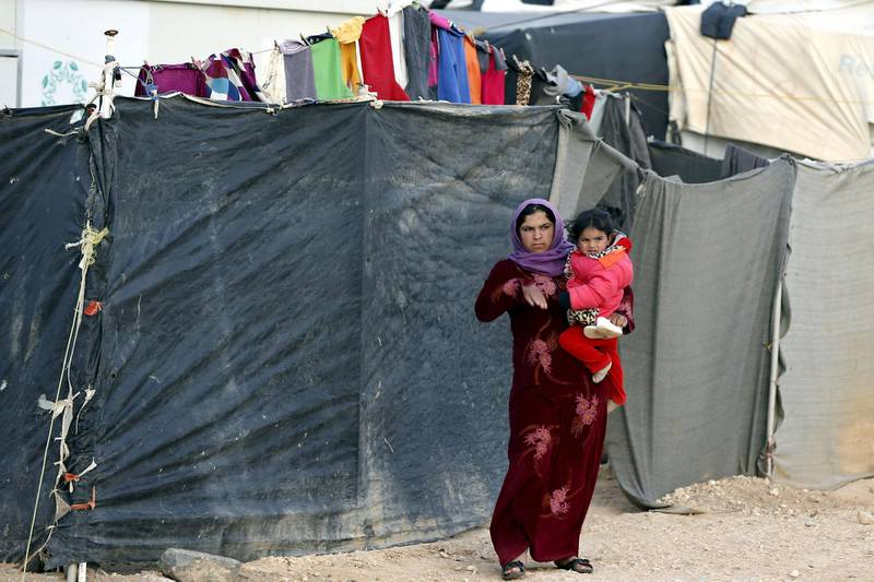 A Syrian refugee woman carrying her child looks at the convoy of U.N. High Commissioner for Refugees (UNHCR) Filippo Grandi as he visits Al Zaatari refugee camp in the Jordanian city of Mafraq, near the border with Syria, January 18, 2016. REUTERS/Muhammad Hamed - GF20000099256