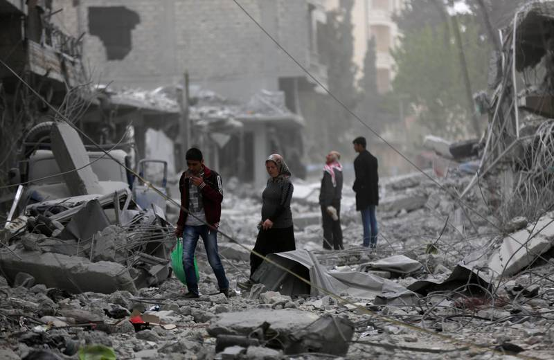 People walk through debris in the center of Afrin, Syria March 24, 2018. REUTERS/Khalil Ashawi