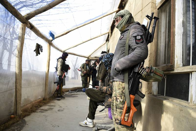 In this photo taken on January 9, 2021, Hazara armed militia for the Resistance for Justice Movement, stand inside their base ahead of a patrol against Taliban insurgents at Hisa-e-Awali Behsud district of Maidan Wardak Province. - Comprising roughly 10 to 20 percent of Afghanistan's 38-million population, Hazaras have long been persecuted for their largely Shiite faith by Sunni hardliners in a country wracked by deep ethnic divisions. (Photo by WAKIL KOHSAR / AFP) / TO GO WITH'Afghanistan-Hazara-violence', by David STOUT, Najiba NOORI