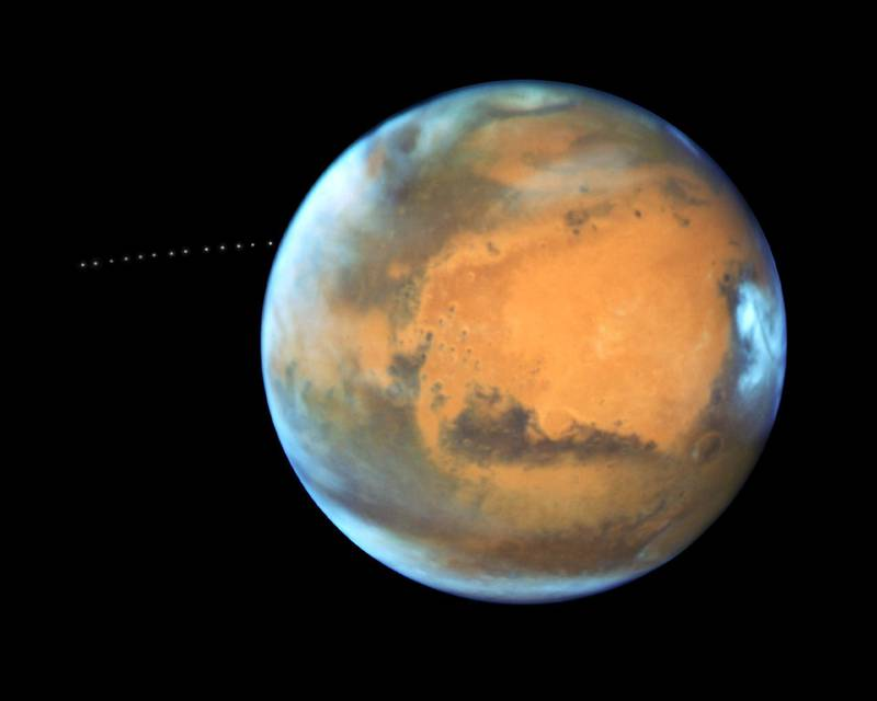 The sharp eye of NASA's Hubble Space Telescope has captured the tiny moon Phobos during its orbital trek around Mars. Because the moon is so small, it appears star-like in the Hubble pictures. The Hubble observations were intended to photograph Mars, and the moon's cameo appearance was a bonus. A football-shaped object just 16.5 miles by 13.5 miles by 11 miles, Phobos is one of the smallest moons in the solar system. It is so tiny that it would fit comfortably inside the Washington, D.C. Beltway. NASA