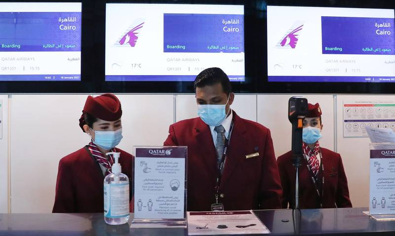 """Qatar Airways employees wait at the boarding counter ahead of the first flight bound for Cairo after the resumption of flights between Qatar and Egypt, at Qatar's Hamad International Airport near the capital Doha on January 18, 2021. Egypt reopened its airspace to Qatari flights on January 18 following a thaw in relations between Doha and a Saudi-led bloc. Egypt in June 2017 joined Saudi Arabia, the United Arab Emirates and Bahrain in cutting ties with Qatar, accusing it of being too close to Iran and backing the Muslim Brotherhood, seen by Cairo and its Gulf allies as a """"terrorist"""" group. Qatar has denied the charges. / AFP / KARIM JAAFAR"""