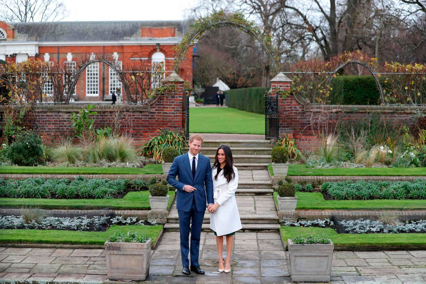 (FILES) In this file photo taken on November 27, 2017 Britain's Prince Harry and his fiancée US actress Meghan Markle pose for a photograph in the Sunken Garden at Kensington Palace in west London on November 27, 2017, following the announcement of their engagement. Kensington Palace, the marital home of Prince Harry and his bride-to-be Meghan Markle, plays host to several royals including his brother Prince William's growing clan. / AFP / Daniel LEAL-OLIVAS