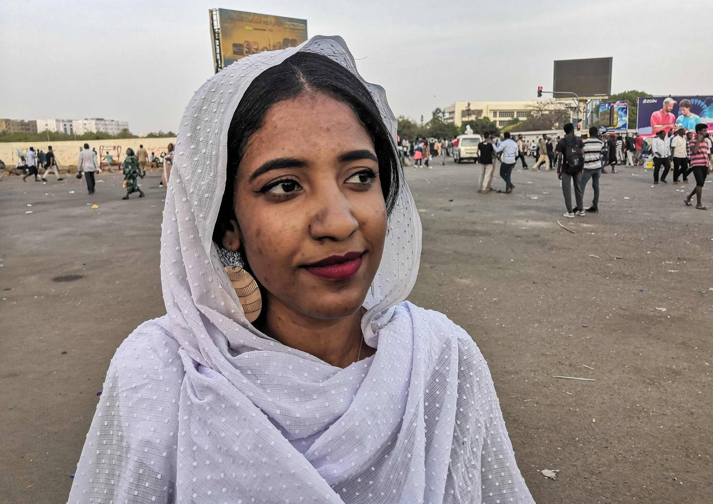 """Alaa Salah, a Sudanese woman propelled to internet fame earlier this week after clips went viral of her leading powerful protest chants against President Omar al-Bashir, attends a demonstration in front of the military headquarters in the capital Khartoum on April 10, 2019. In the clips and photos, the elegant Salah stands atop a car wearing a long white headscarf and skirt as she sings and works the crowd, her golden full-moon earings reflecting light from the fading sunset and a sea of camera phones surrounding her. Dubbed online as """"Kandaka"""", or Nubian queen, she has become a symbol of the protests which she says have traditionally had a female backbone in Sudan.  / AFP / -"""