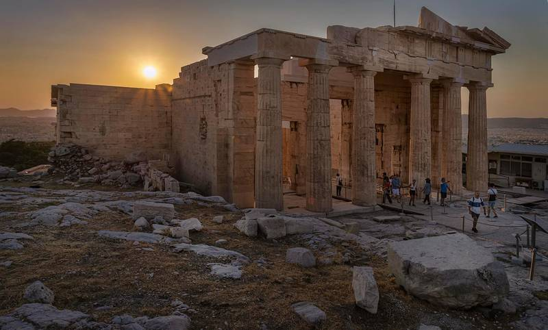 Sunset at the Acropolis, with the entrance Propylaea in the foreground and tourists around, Athens, Greece. Getty Images