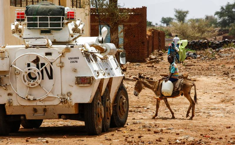 A Sudanese boy rides a donkey past a UN-African Union mission in Darfur (UNAMID) armoured vehicle in the war-torn town of Golo in the thickly forested mountainous area of Jebel Marra in central Darfur on June 19, 2017. The town was a former rebel bastion which was recently captured by Sudanese government forces. - The United States' top envoy in Sudan visited Golo on June 19, 2017 on the second day of his four-day trip to Darfur to assess security in the war-torn region as the UN prepares to downsize its 17,000-strong peacekeeping force.  His visit also comes just weeks before President Donald Trump's administration decides whether to permanently lift a two-decades old US trade embargo on Sudan. (Photo by ASHRAF SHAZLY / AFP)
