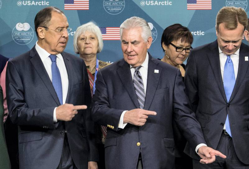 US Secretary of State Rex Tillerson (C) shows the way out to Russian Foreign Minister Sergei Lavrov (L) after posing for a family photo at the Arctic Council meeting in Fairbanks, Alaska, on May 11, 2017. / AFP PHOTO / NICHOLAS KAMM