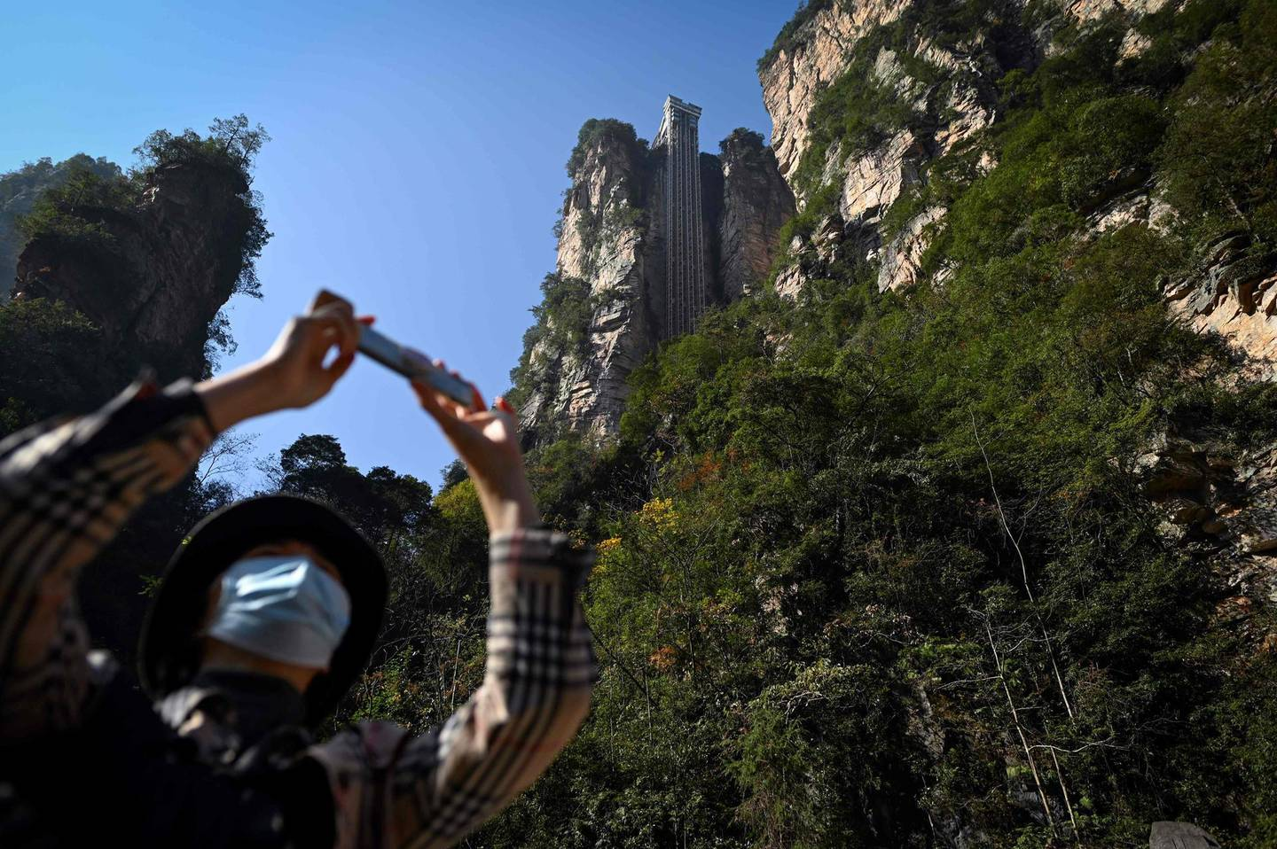 """This picture taken on November 13, 2020 shows a tourist with a face mask using her mobil phone to take a picture at the entrance of the Bailong elevators in Zhangjiajie, China's Hunan province.   Towering more than 300 metres (1,000 feet) up the cliff face that inspired the landscape for the blockbuster movie """"Avatar"""", the world's highest outdoor lift whisks brave tourists to breathtaking views. - TO GO WITH: China technology film tourism transport, by Ludovic EHRET  / AFP / WANG ZHAO / TO GO WITH: China technology film tourism transport, by Ludovic EHRET"""