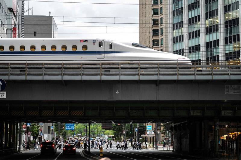 People cross a street while a shinkansen, or high speed bullet train, leaves Tokyo on June 16, 2021. / AFP / Charly TRIBALLEAU