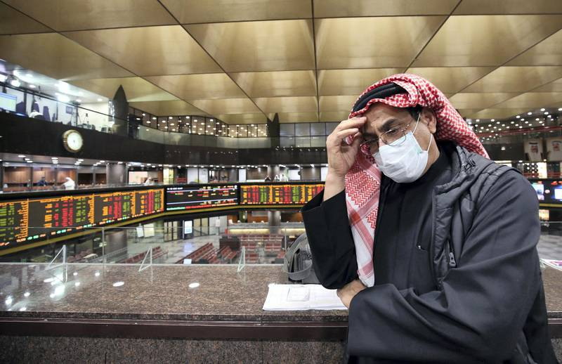 A Kuwaiti trader wearing a protective mask follows the market at the Boursa Kuwait stock exchange in Kuwait City on March 1, 2020. - Boursa Kuwait decided to close the main trading hall due to the COVID-19 coronavirus disease developments. Stock markets in the oil-rich Gulf states plunged on March 1 over fears of the impact of the coronavirus, which also battered global bourses last week. All of the seven exchanges in the Gulf Cooperation Council (GCC), which were closed the previous two days for the Muslim weekend, were hit as oil prices dropped below $50 a barrel. The region's slide was led by Kuwait Boursa, where the All-Share Index fell 10 percent, triggering its closure. Kuwait's bourse was closed for most of last week for national holidays. (Photo by YASSER AL-ZAYYAT / AFP)