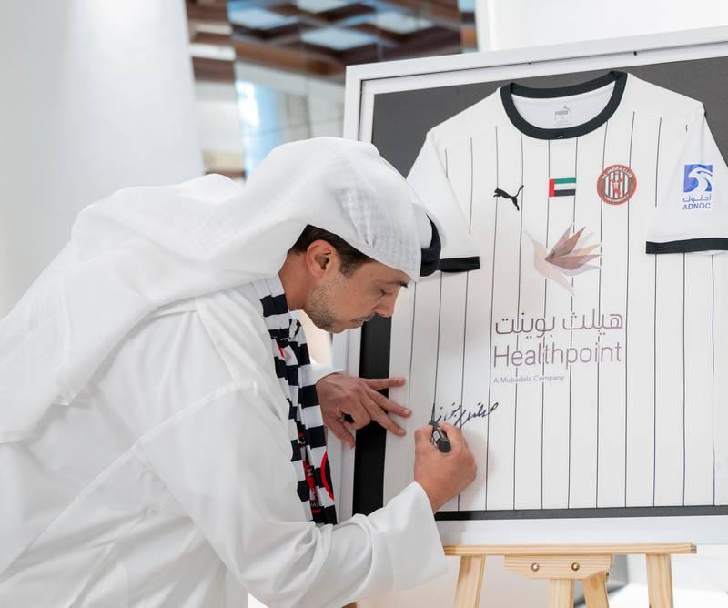 ABU DHABI, UNITED ARAB EMIRATES - June 03, 2021: HH Sheikh Mansour bin Zayed Al Nahyan, UAE Deputy Prime Minister and Minister of Presidential Affairs (C) signs   Al Jazira Football Club shirt, who won the 2020/21 Arabian Gulf League title, at Al Shati Palace.  ( Mohamed Al Hammadi / Ministry of Presidential Affairs ) ---