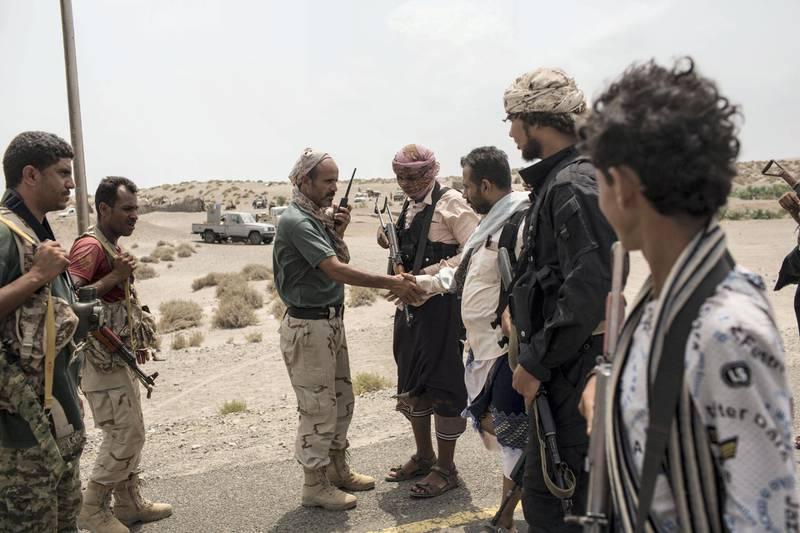 An army officer of the Tarik Salih' brigade (3rdL) shakes hands with Ahmed Al- Kawkabani, the leader of Tuhama Brigade,  3rd R , close to a front line in al-Hudayda outskirts as they discuss the advance of their joined troops fighting the Houthis, along the west coast. May 15, 2018.  Photo/ Asmaa Waguih