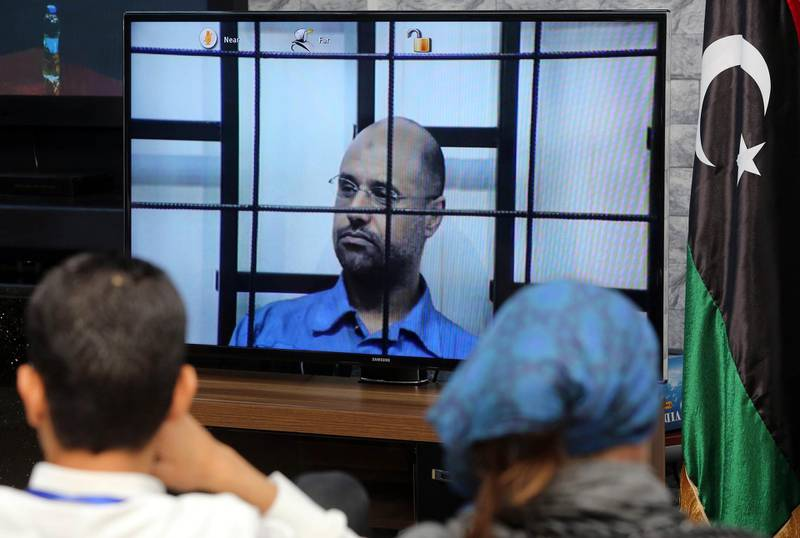 (FILES) In this file photo taken on April 27, 2014 Journalists watch as the judges (unseen), question Seif al-Islam (C), the son of slain Libyan dictator Moamer Kadhafi, broadcasted live from the western Libyan city of Zintan, from inside a room in Tripoli. Nearly a year after a Libyan militia announced it had set free the son and heir apparent of slain dictator Moamer Kadhafi, the fate of Seif al-Islam remains a mystery. / AFP PHOTO / Mahmud TURKIA