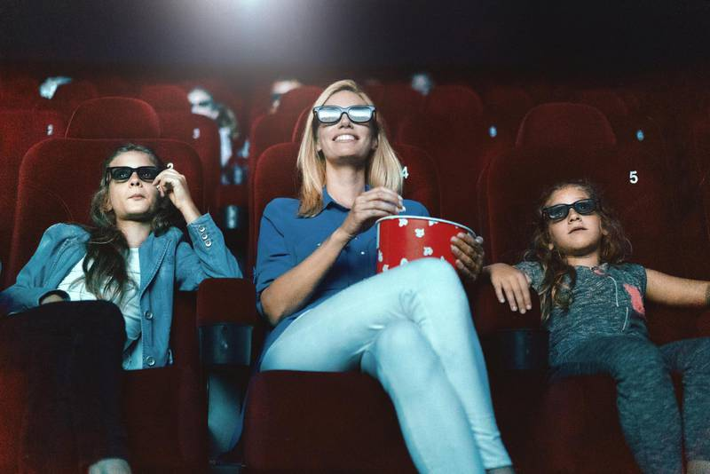 Closeup low angle view of a single mom watching a movie at a movie theater with her daughters. They are sitting in the front row, eating popcorn and wearing a 3d glasses.