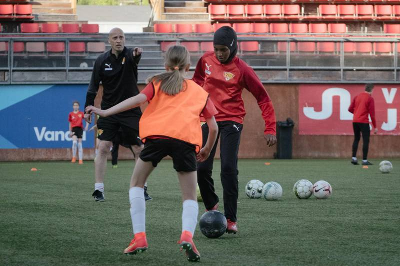 """Kamila Nuh (R), wearing a sports hijab, plays the ball as she attends a football training session at the MUP Stadium in Vantaa, Finland, on June 1, 2021.   Finland's football association has begun offering a free """"sports hijab"""" to any player who wants one, in a move designed to attract a greater diversity of players into the sport. So far, the FA has distributed """"dozens"""" of the headscarves, which are made out of technical, stretchy fabric, Heidi Pihlaja, head of development of women and girls' football, told AFP.   / AFP / Alessandro RAMPAZZO"""