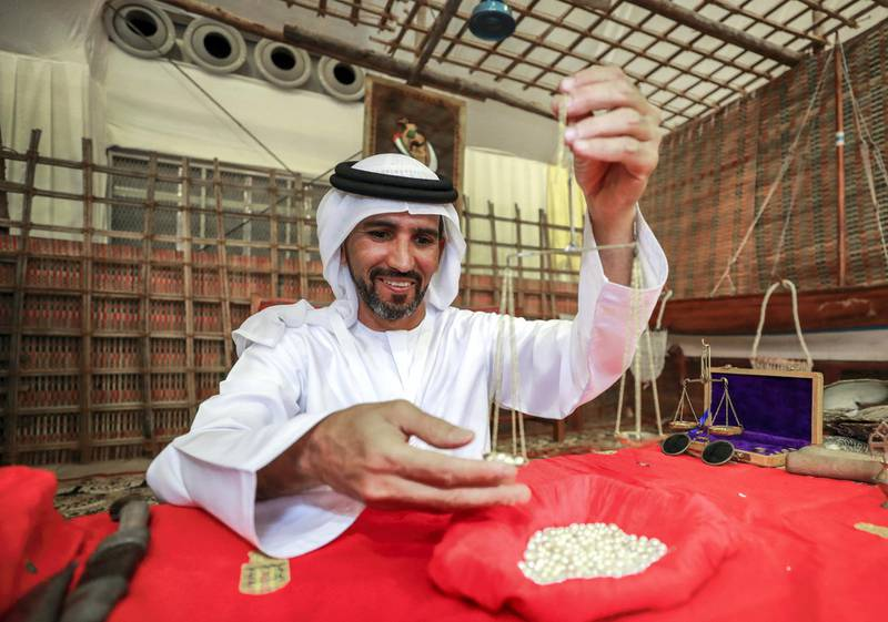 Abu Dhabi, U.A.E., July 18, 2018.  First day of the 2018 Liwa Date Festival.   Mohamed Ateeq Almehairbi, Emirates Heritage Club  weighs some pears at the festival.Victor Besa / The NationalSection:  NAReporter:  Haneen Dajani