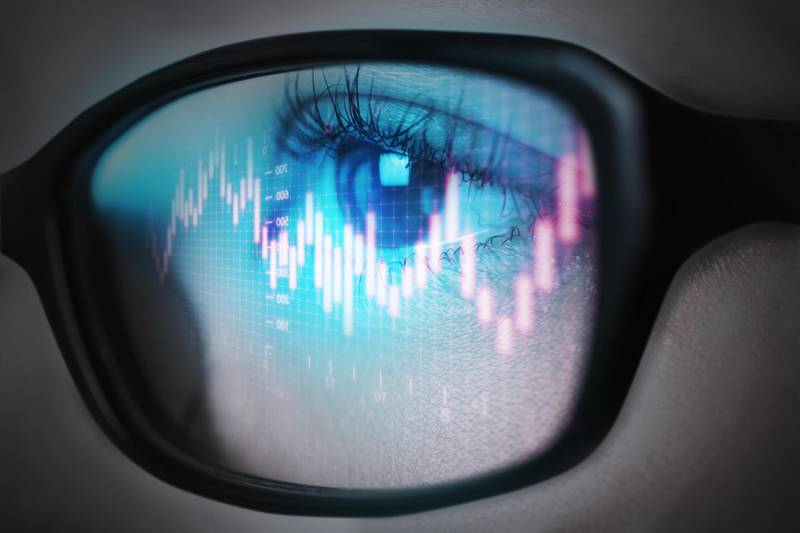 The reflection of the stock graph on a young adult women's glasses. Getty Images