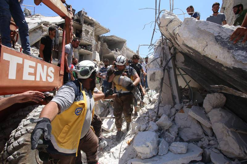 """Members of the Syrian civil defence, known as the White Helmets, pull out an injured but alive child from under the rubble following a Russian air strike on Maaret al-Numan in Syria's northwestern Idlib province on July 22, 2019 in the latest violence to plague the opposition bastion, as the Damascus regime and its Russian ally have stepped up their deadly bombardment of Idlib since late April. Sixteen civilians were among 19 people killed and at least 45 others were wounded in the air raid that hit """"a wholesale vegetable market in the town of Maaret al-Numan"""", according to the Syrian Observatory for Human Rights. The death toll could still rise as many of those wounded are in a critical condition and some people are still trapped under rubble, the Britain-based monitor said.  / AFP / Abdulaziz KETAZ"""