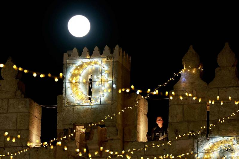 TOPSHOT - April's full moon, known as the Super Pink Moon, rises over the Damascus gate as an Israeli police stands guard in Jerusalem's Old City on April 27, 2021. / AFP / Menahem KAHANA