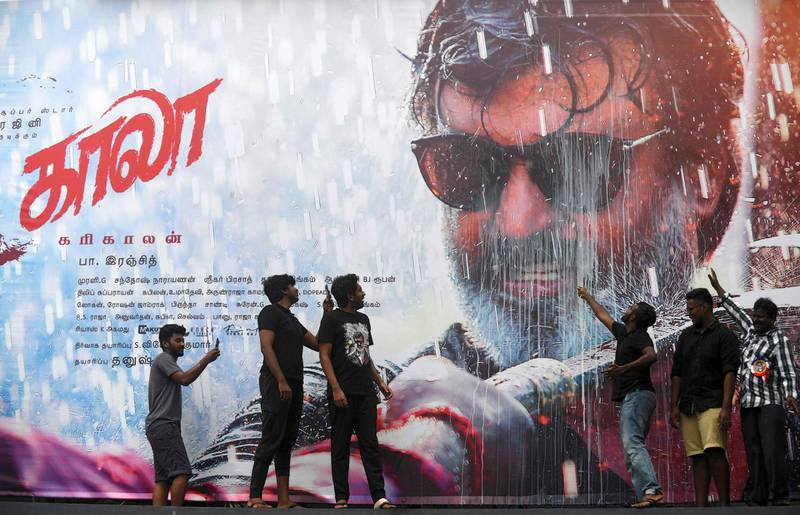 """Indian fans pose and take pictures as they celebrate next to a poster of Bollywood star Rajinikanth outside a cinema on the first day of release of his new Tamil-language film """"Kaala"""", in Chennai on June 7, 2018. Rajinikanth's film """"Kaala"""" is released on June 7 across the country except in Karnataka as Pro-Kannada groups have been upset with Rajinikanth's remarks on the Cauvery water dispute between Karnataka and Tamil Nadu. / AFP / Arun SANKAR"""