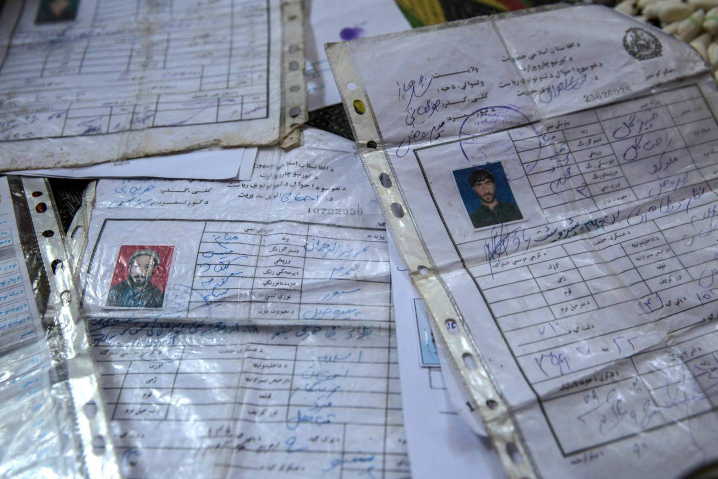ID cards of the seven peple from Jawari village who were killed in a US drone strike lie on the floor of Rahat Gul's house.