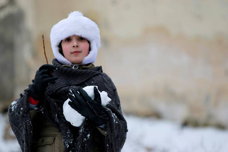 A girl carries a snow ball while playing in Aleppo January 11, 2015. A storm buffeted the Middle East with blizzards, rain and strong winds, keeping people at home across much of the region and raising concerns for Syrian refugees facing freezing temperatures in flimsy shelters. The storm is forecast to last several days, threatening further disruption in Lebanon, Syria, Turkey, Jordan, Israel, the West Bank and the Gaza Strip, which have all been affected REUTERS/Hamid Khatib (SYRIA - Tags: SOCIETY ENVIRONMENT)