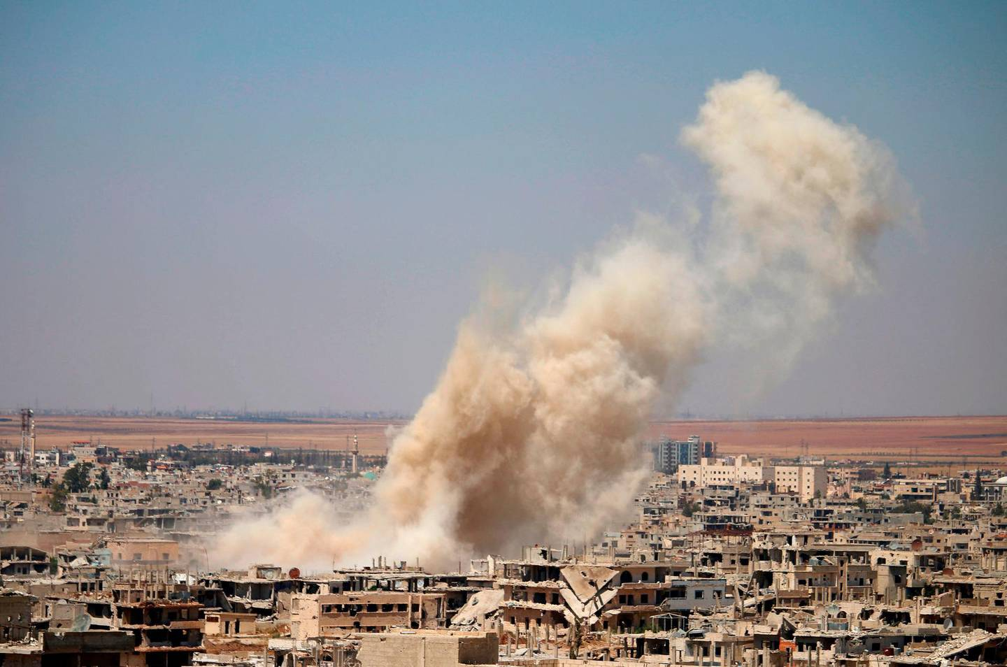 Smoke rises above opposition held areas of Daraa during an airstrike by Syrian regime forces, on June 25, 2018. Russian-backed regime forces have for weeks been preparing an offensive to retake Syria's south, a strategic zone that borders both Jordan and the Israeli-occupied Golan Heights. / AFP / Mohamad ABAZEED