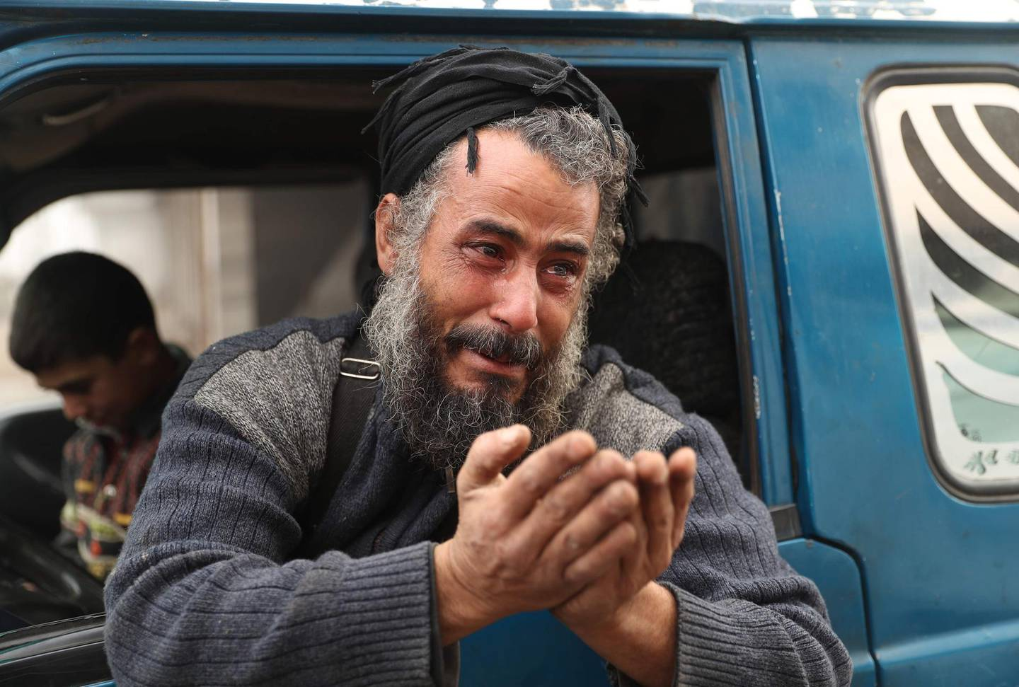 TOPSHOT - Abu Ahmad, one of the last people to flee from Maaret al-Numan in the northwestern Syrian Idlib province, reacts as he rides in a pick-up truck before leaving the town with his family towards a camp for the displaced, on December 24, 2019. Syrian government forces on December 24 were less than four kilometres (two miles) from the strategic city of Maaret al-Numan, the head of the Britain-based monitor, Rami Abdel Rahman, told AFP. Fearing further advances, thousands of Maaret al-Numan's residents have fled.  / AFP / Omar HAJ KADOUR