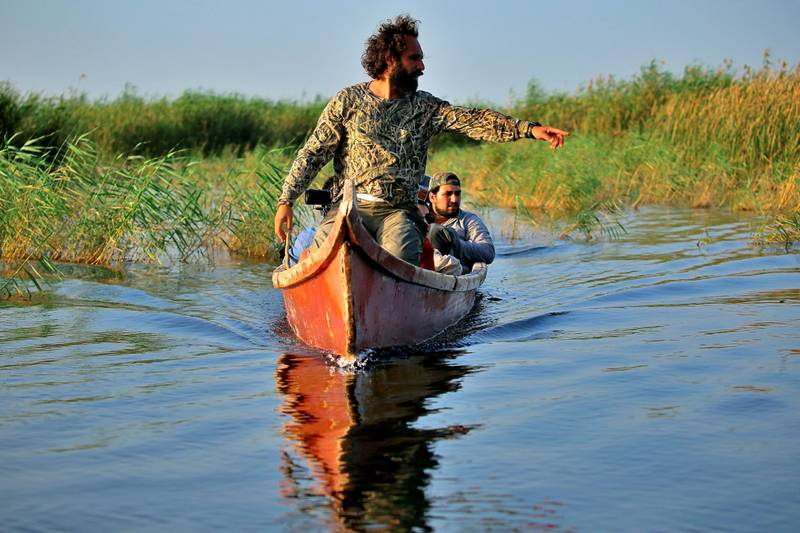 Environmentalist Omar al-Sheikhly leads a team into the marshes in search of endangered animals, in Chibayish, Iraq, Saturday, May, 1, 2021. Deep within Iraq's celebrated marsh lands, conservationists are sounding alarm bells and issuing a stark warning: Without quick action, the UNESCO protected site could all but wither away. (AP Photo/Anmar Khalil)