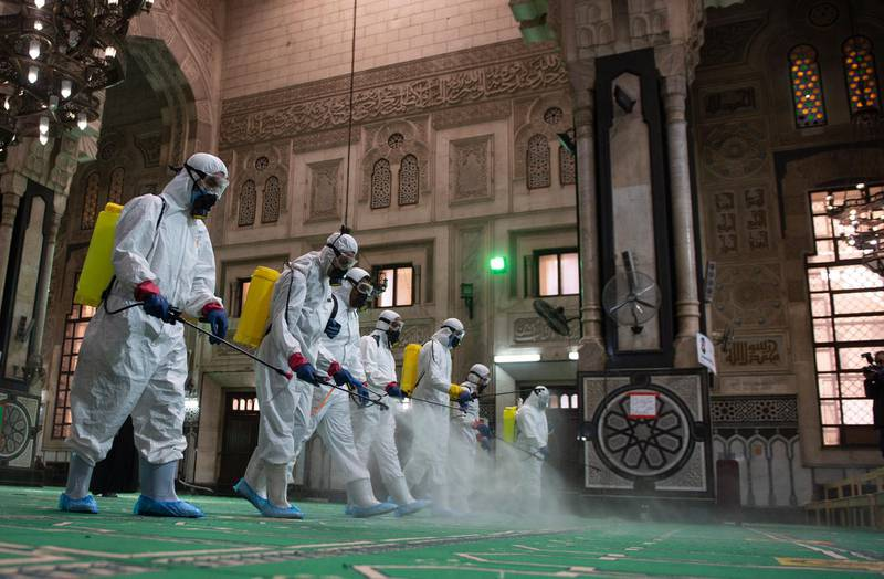 epa09126527 Workers wearing protective suits spray disinfectant in al-Fateh mosque as it is being prepared for prayers during the holy month of Ramadan, following the outbreak of the coronavirus disease (COVID-19), in Cairo, Egypt, 10 April 2021. Muslims around the world celebrate the holy month of Ramadan by praying during the night time and abstaining from eating, drinking, and sexual acts during the period between sunrise and sunset. Ramadan is the ninth month in the Islamic calendar and it is believed that the revelation of the first verse in Koran was during its last 10 nights.  EPA/Mohamed Hossam