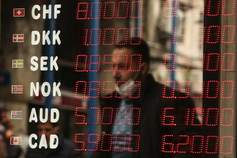 A man is reflected at a foreign currency board in a currency exchange shop, in Istanbul, Monday, March 22, 2021. The Turkish currency plummeted against the U.S. dollar on Monday after President Recep Tayyip Erdogan fired the central bank governor over the weekend for hiking interest rates. The lira was trading at around 7.9 against the dollar — nearly 10% down from Friday's close. Erdogan, who advocates keeping interest rates low to tame inflation, unexpectedly fired Naci Agbal with a decree on Saturday, just four months after he took office. (AP Photo/Emrah Gurel)