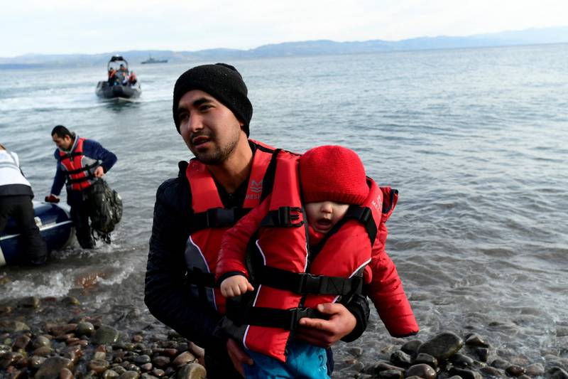 A migrant holds a baby as they arrive at the village of Skala Sikaminias, on the Greek island of Lesbos, after crossing the Aegean sea from Turkey, on Friday, Feb. 28, 2020. An air strike by Syrian government forces killed scores of Turkish soldiers in northeast Syria, a Turkish official said Friday, marking the largest death toll for Turkey in a single day since it first intervened in Syria in 2016. (AP Photo/Micheal Varaklas)