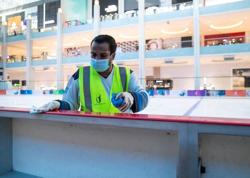 DUBAI, UNITED ARAB EMIRATES. 11 JUNE 2020. Babki sanitizes the railing at the Ice Rink in Dubai Mall.(Photo: Reem Mohammed/The National)Reporter:Section: