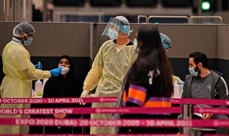 Health workers check passengers who arrived on an Emirates Airlines flight from London at   Dubai International Airport on May 8, 2020 amid the coronavirus Covid-19 pandemic.         / AFP / Karim SAHIB