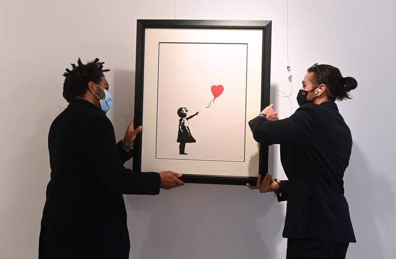epa09152364 Gallery workers adjust an artwork by British artist, Banksy 'Girl with a baloon' at the 'Millennials' exhibition at the Hofa gallery in London London, Britain, 22 April 2021. The new exhibition features artists such as Banksy, Nina Chanel Abney, Jonas Wood, Josh Sperling, Yoshimoto Nara and will open to the public on 23 April.  EPA/FACUNDO ARRIZABALAGA