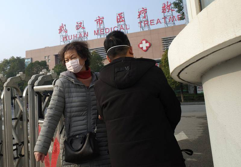 A woman (L) leaves the Wuhan Medical Treatment Centre, where a man who died from a respiratory illness was confined, in the city of Wuhan, Hubei province, on January 12, 2020. - A 61-year-old man has become the first person to die in China from a respiratory illness believed caused by a new virus from the same family as SARS, which claimed hundreds of lives more than a decade ago, authorities said. (Photo by Noel Celis / AFP)