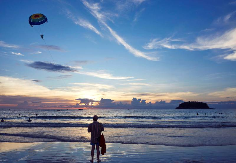 KATA BEACH, PHUKET, THAILAND - 2017/11/21: A beachgoer watches parasailing off the beach in Phuket. Tourists can take short parasailing flights from the beach out toward the small island, Koh Pu, and back again.  Phuket attracts more than 5 million tourists each year who flock there for it's picturesque beaches. (Photo by Craig Ferguson/LightRocket via Getty Images)