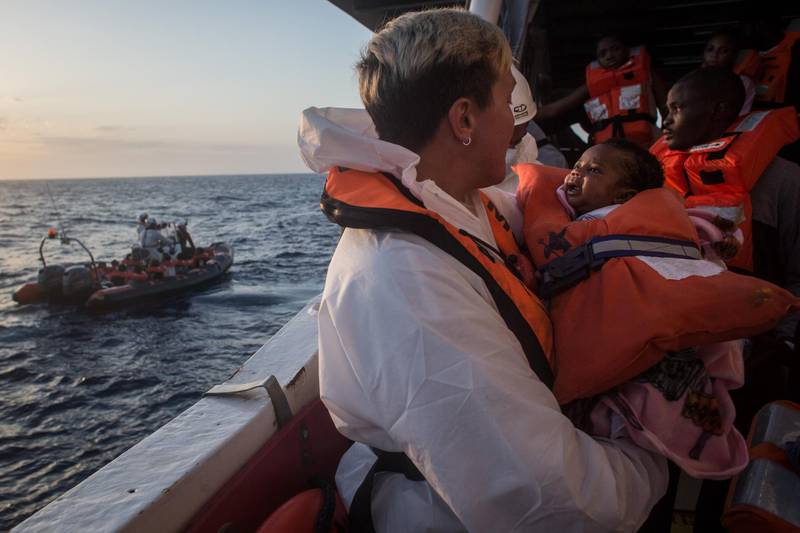 LAMPEDUSA, ITALY - JUNE 10: A crewmember from the Migrant Offshore Aid Station (MOAS) Phoenix vessel holds a child as they wait to transfer refugees and migrants to a waiting Italian coastguard ship after being rescued at sea earlier in the day on June 10, 2017 off Lampedusa, Italy. An estimated 230,000 refugees and migrants will arrive in Italy this year as numbers of refugees and migrants attempting the dangerous central mediterranean crossing from Libya to Italy continues to rise since the same time last year. So far this year more than 58,000 people have arrived in Italy and 1,569 people have died attempting the crossing. Libya continues to be the primary departure point for refugees and migrants taking the central mediterranean route to Sicily. In an attempt to slow the flow of migrants, Italy recently signed a deal with Libya, Chad and Niger outlining a plan to increase border controls and add new reception centers in the African nations, which are key transit points for migrants heading to Italy. MOAS is a Malta based NGO dedicated to providing professional search-and-rescue assistance to refugees and migrants in distress at sea. Since the start of the year MOAS have rescued and assisted more than 4000 people and are currently patrolling and running rescue operations in international waters off the coast of Libya.  (Photo by Chris McGrath/Getty Images)