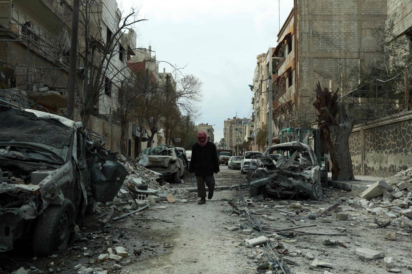 A picture taken on February 25, 2018, shows a Syrian man walking next to damaged buildings following regime air strikes in the Syrian rebel-held town of Douma, in the besieged Eastern Ghouta region on the outskirts of the capital Damascus. New regime air strikes and heavy clashes shook Syria's rebel enclave of Eastern Ghouta on Sunday despite a UN demand for a ceasefire to end one of the most ferocious assaults of Syria's civil war. / AFP PHOTO / HAMZA AL-AJWEH