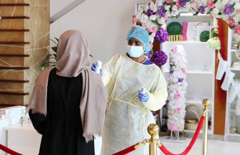 DUBAI, UNITED ARAB EMIRATES , April 26– 2020 :- Medical staff checking the temperature of the visitor at the entrance of the Prime Hospital on airport road in Al Garhoud in Dubai . (Pawan Singh / The National) For News/Standalone/Online/Instagram/Stock.  Story by Nick Webster