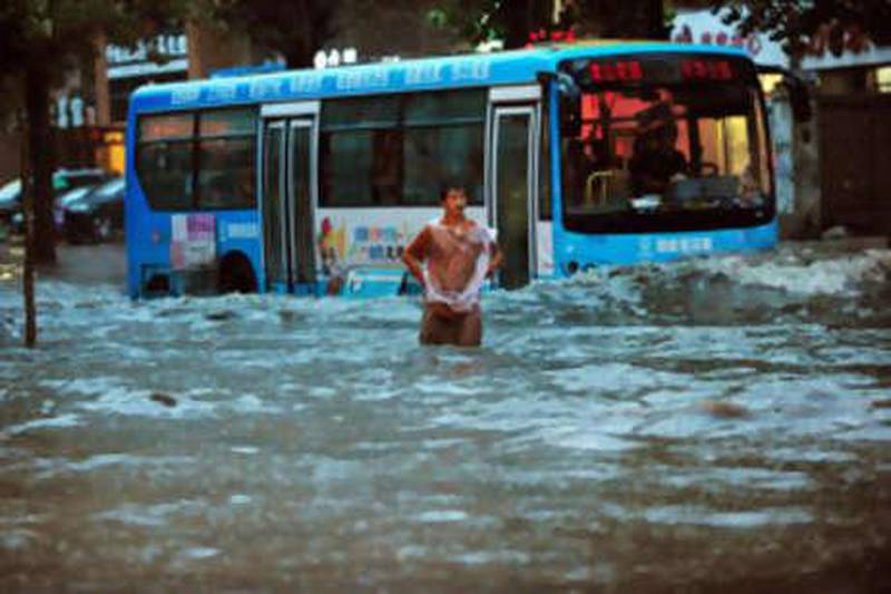 epa02295714 A photograph made available on 22 August 2010 shows a man standing on a heavily flooded street  as a public bus drives by, in Shenyang, China's North East Liaoning province on 21 August 2010. Chinese media has reported four deaths after Liaoning province was hit by torrential rains, causing China's North Eastern Yalu River, which borders North Korea, to overflow. Over 64,000 people were forced to evacuate their homes 21 August, as waters did not recede.  EPA/MARK