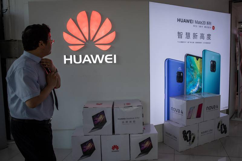 epa07586410 A man walks next to a Huawei logo in a shopping mall in Beijing, China, 20 May 2019. According to media reports on 20 May 2019, the US based multinational technology company Google halted business with Huawei in the wake of the Trump administration adding the Chinese telecommunication company to a trade blacklist over national security concerns. Huawei will lose access to updates for the Android operating system.  EPA-EFE/ROMAN PILIPEY *** Local Caption *** 55208626