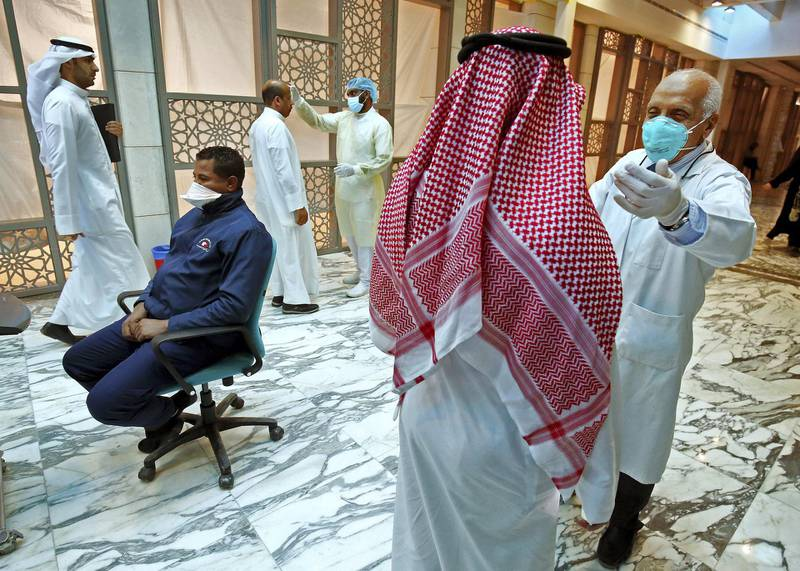 Kuwaiti health ministry workers scan employees and visitors of the ministries complex, as they arrive to their work, in Kuwait City on March 4, 2020. (Photo by YASSER AL-ZAYYAT / AFP)
