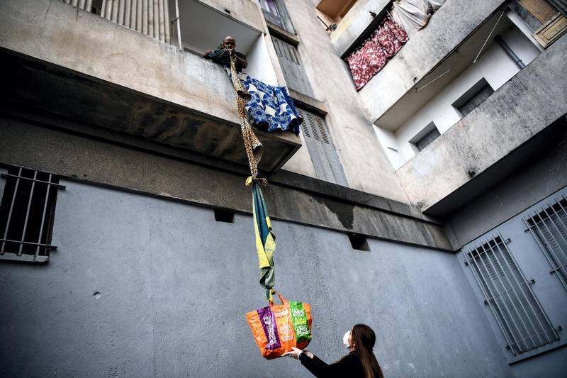 An inhabitant of the residence Maison Blanche (White House residence), composed of 226 mostly unsanitary dwellings, collects food offered by neighbours from his balcony, using a rope made with blankets, on March 31, 2020, in Marseille, southern France, on the fifteenth day of a lockdown aimed at curbing the spread of the COVID-19 (novel coronavirus). (Photo by Anne-Christine POUJOULAT / AFP)