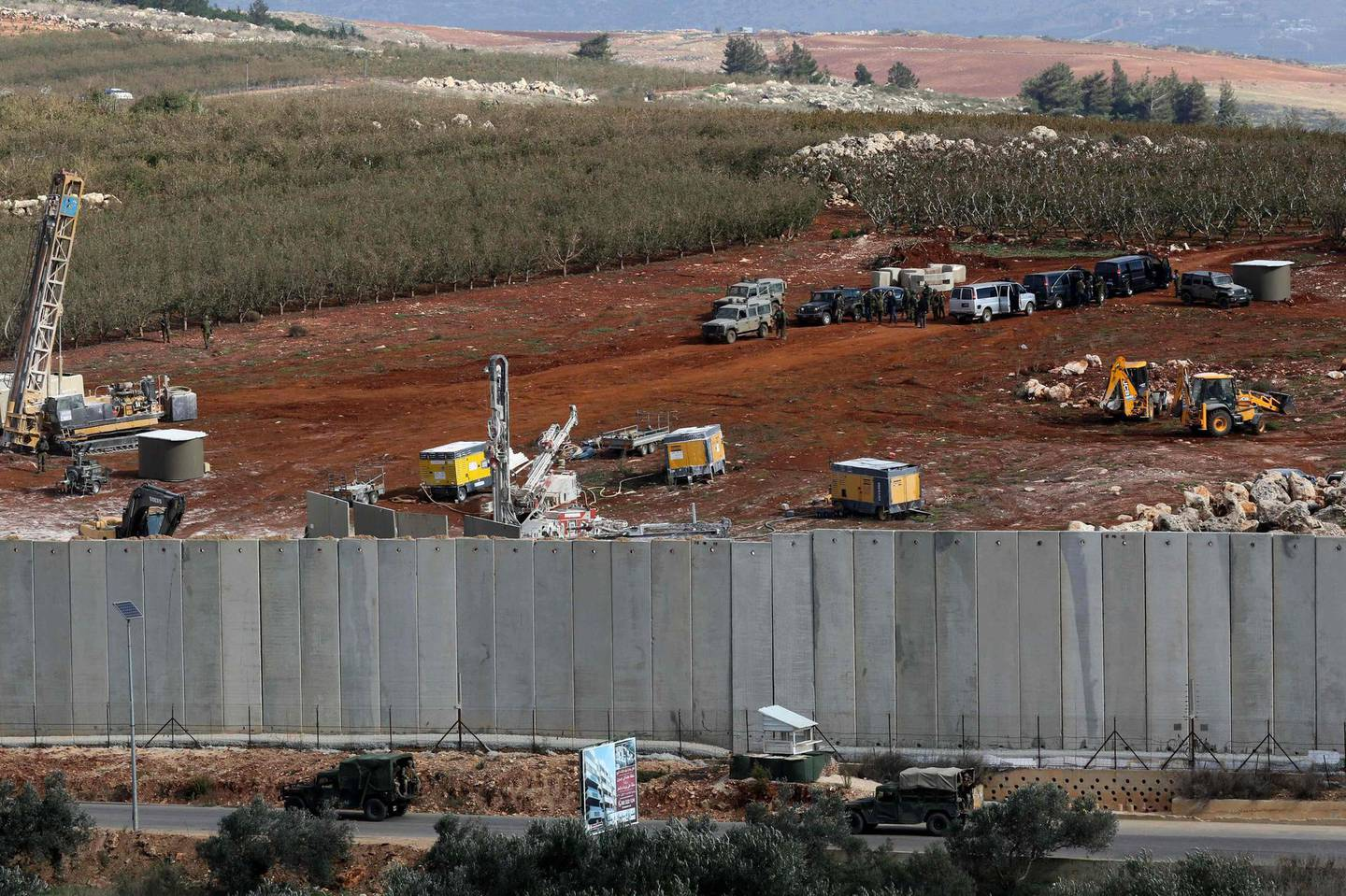 A picture taken on December 5, 2018 in the southern Lebanese village of Kfar Kila near the border with Israel shows Israeli machinery (top) operating next to the concrete border wall. Israel had announced on December 4 that it had discovered Hezbollah tunnels infiltrating its territory from Lebanon and launched an operation to destroy them. / AFP / Mahmoud ZAYYAT